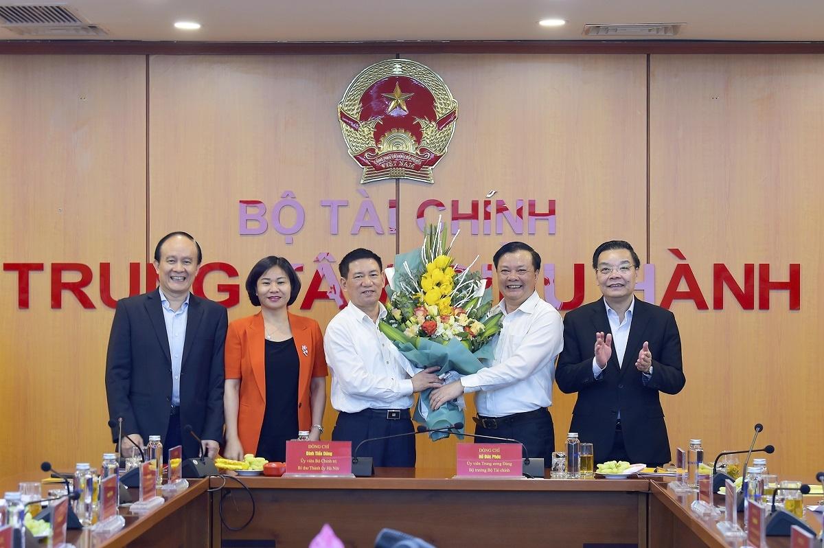Các đồng chí Thường trực Thành ủy Hà Nội tặng hoa Bộ trưởng Hồ Đức Phớc và Bí thư Thành ủy Hà Nội Đinh Tiến Dũng.