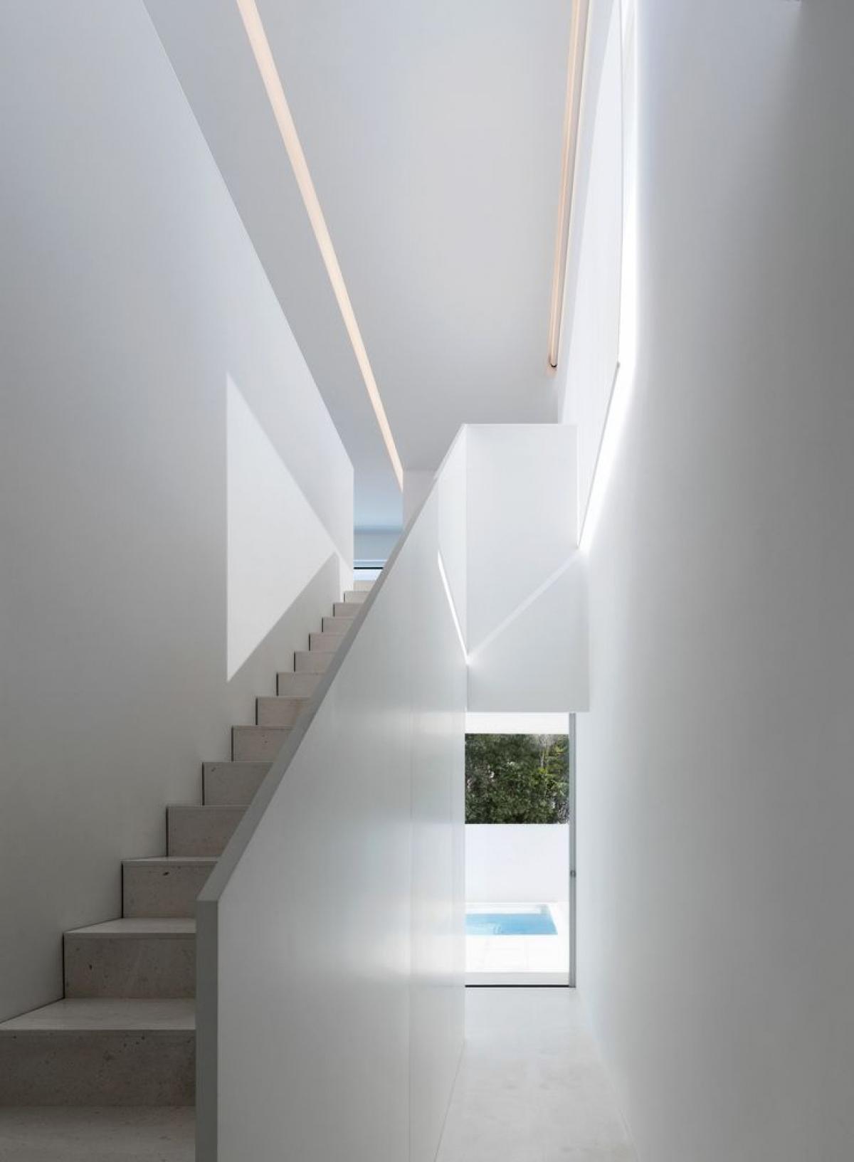 """Cầu thang ở góc nhà lên tầng 2 cũng rất đơn giản. Ánh sáng là một loại """"vật liệu"""" làm nổi bất những hình khối kiến trúc."""