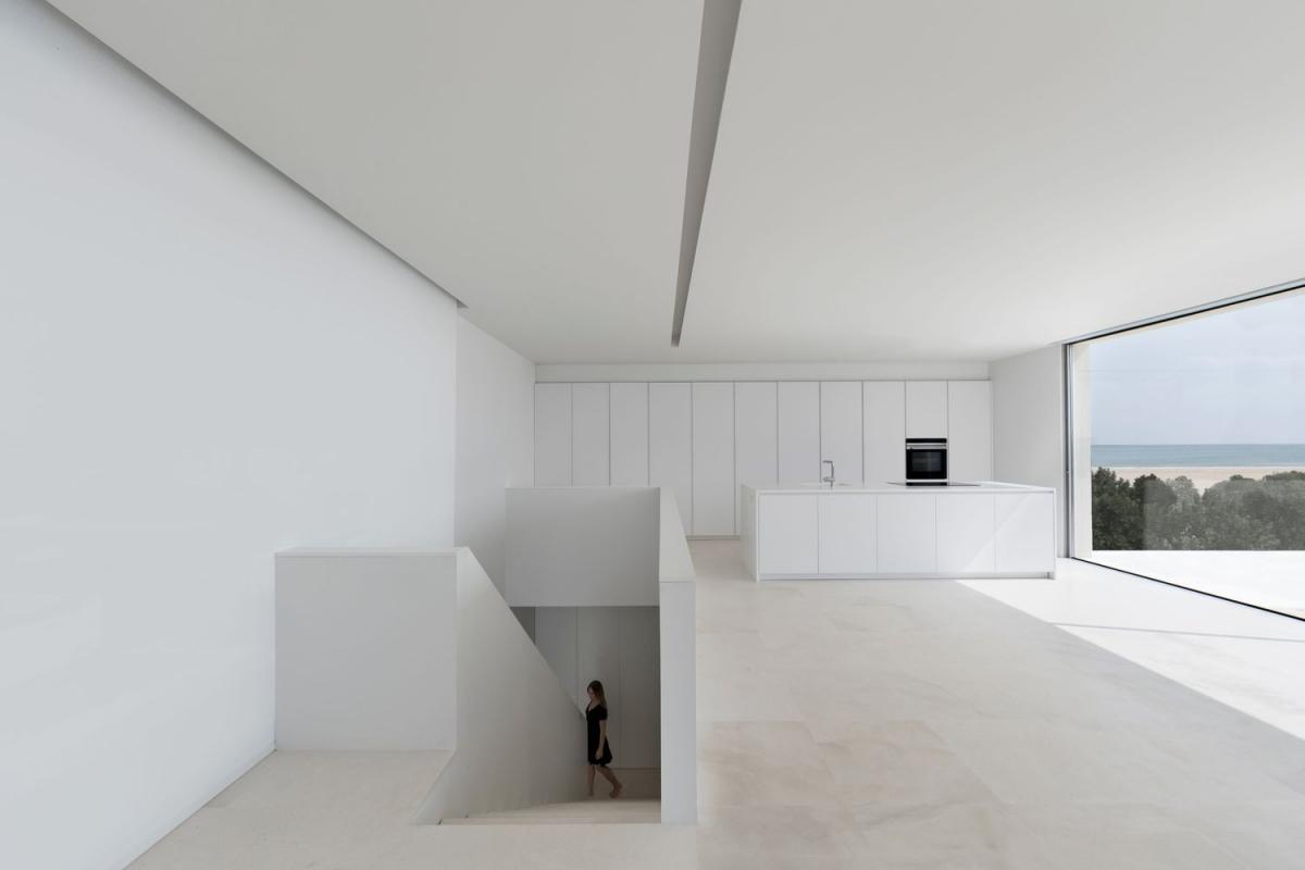 Khu vực bếp nấu cũng toàn màu trắng với nội thất tối giản. Điểm nhấn duy nhất là chiếc lò nướng màu đen. Hệ tủ được thiết kế âm tường, phía ngoài là đảo bếp. Từ không gian lớn trên tầng 2 có thể nhìn thấy biển phía xa.