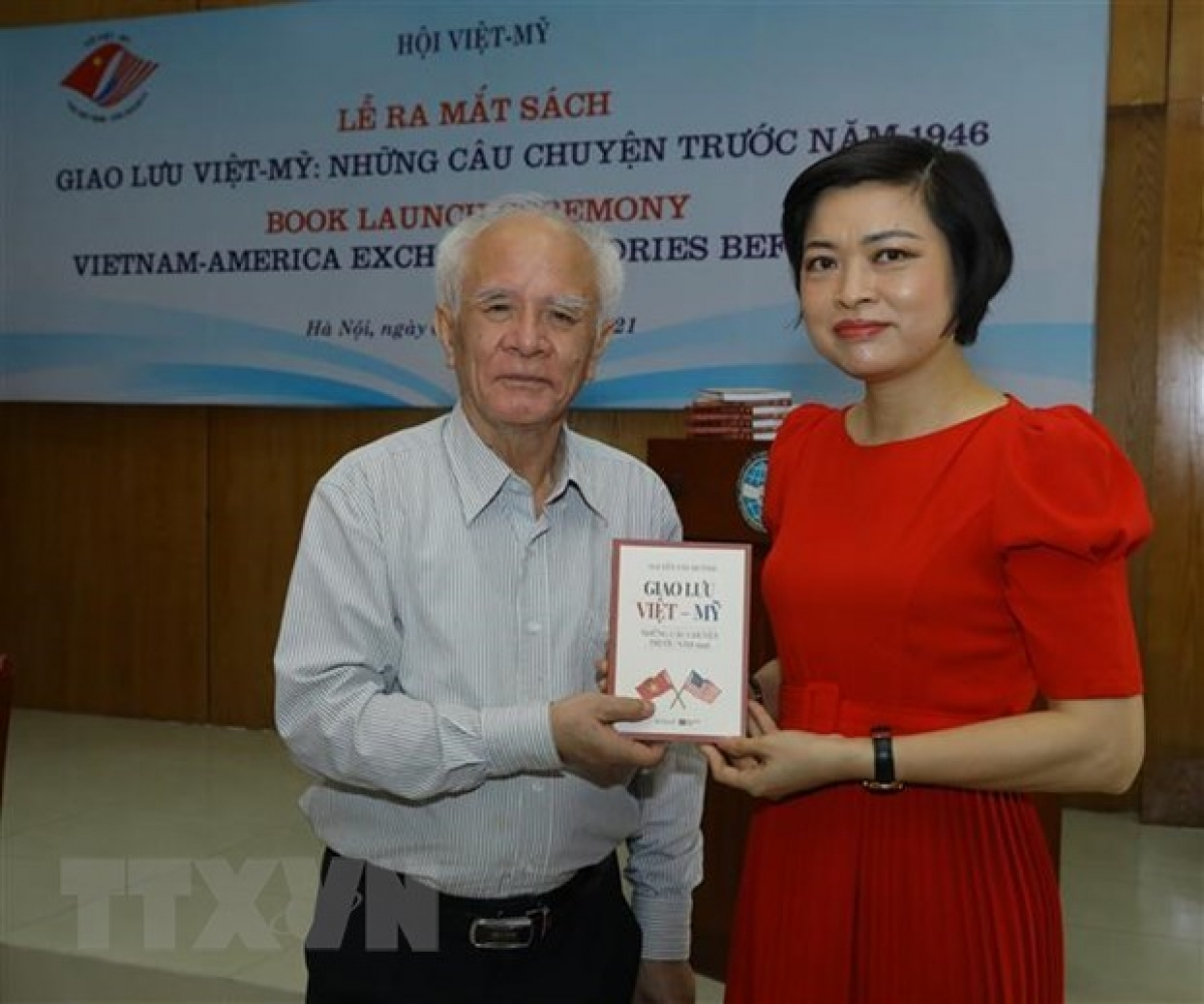 """Nguyen Van Huynh (L) presents his book, titled """"Vietnam-America exchanges: Stories before 1946"""" to a guest at the book launch"""