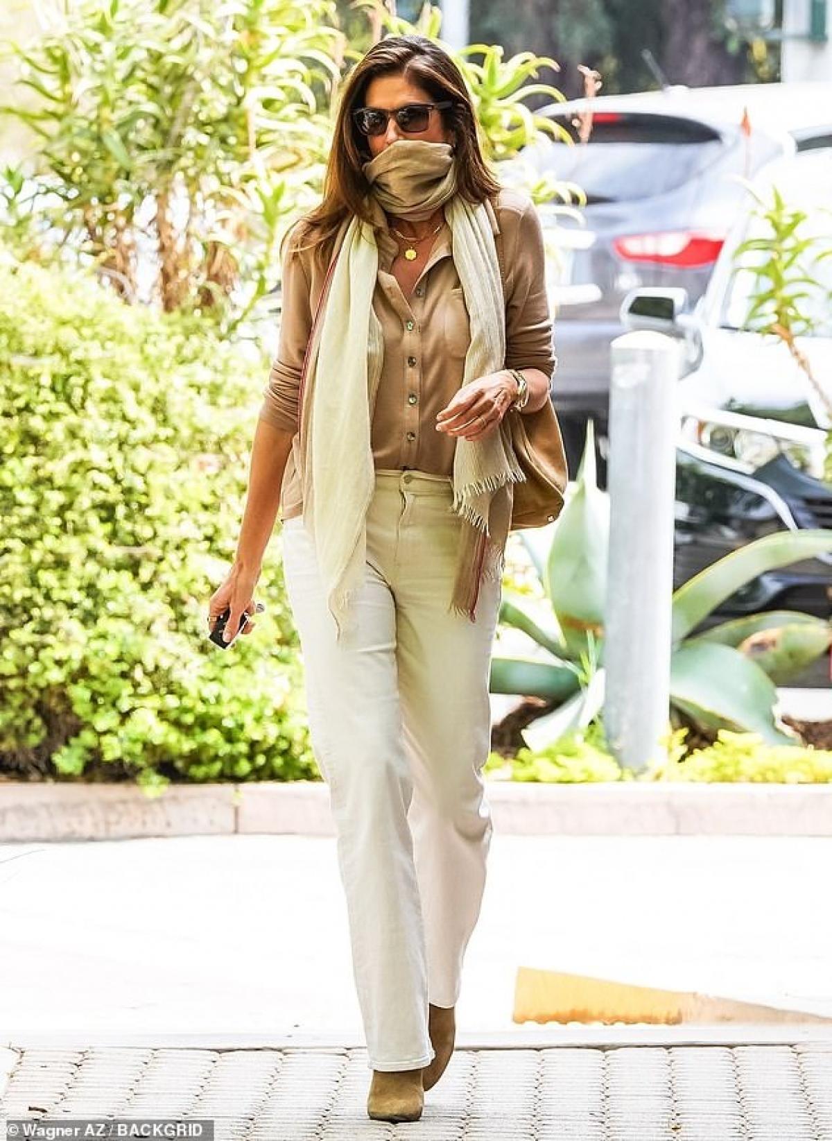 Siêu mẫu huyền thoại diện áo sơ mi và quần suông thanh lịch. Cô dùng khăn thay cho khẩu trang khi ra phố.