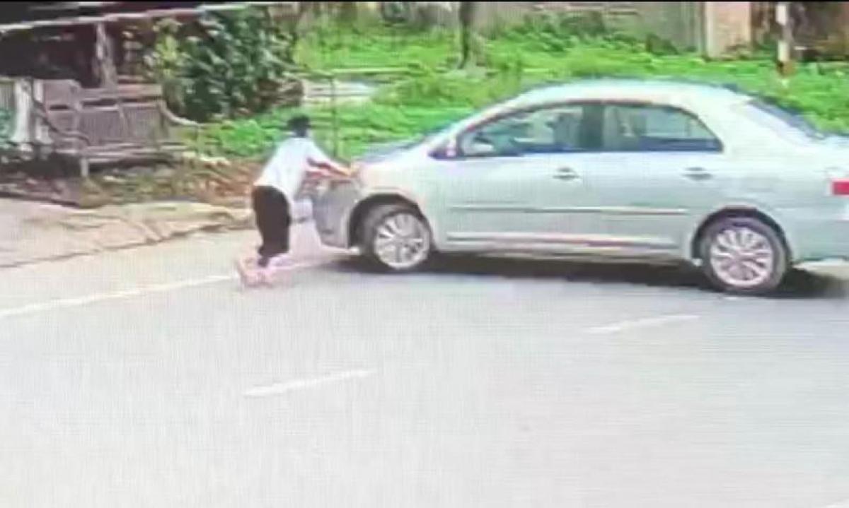 Hình ảnh bé gái chặn trước đầu xe ô tô của kẻ mua 2 két bia không trả tiền.