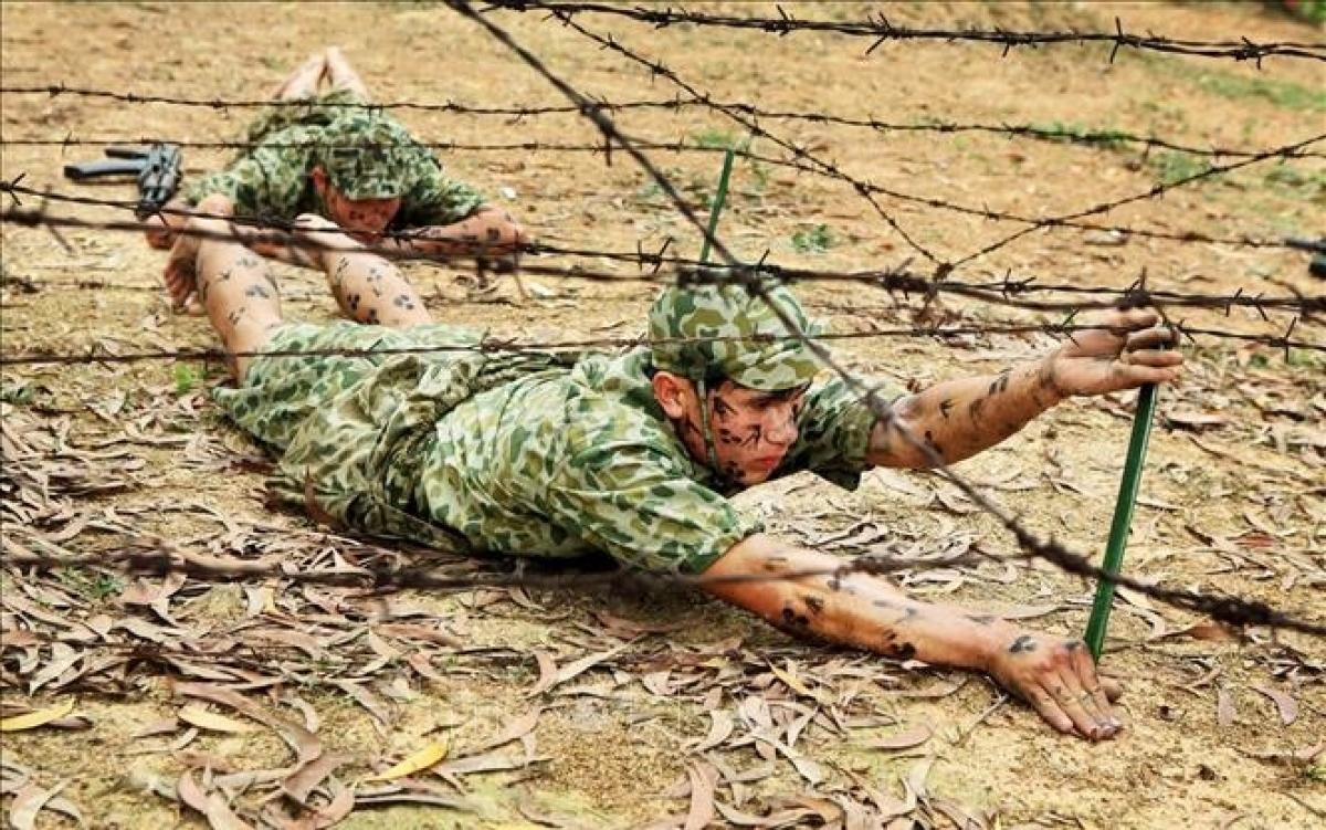 Chiến sĩ đặc công Việt Nam thực hành khắc phục vật cản, trườn qua dây thép gai. Ảnh: Thông tấn xã Việt Nam.