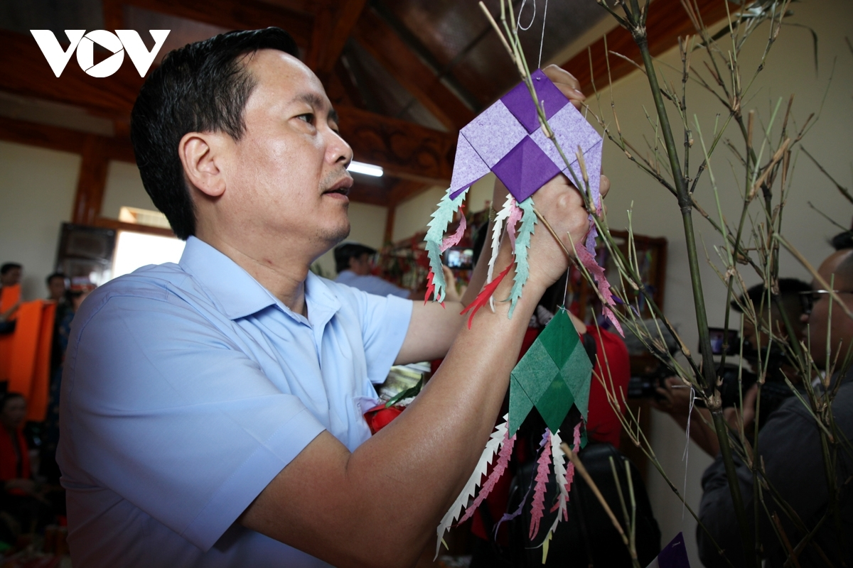 A participant hangs a small paper kite on a branch as they pray for good luck during the new harvest.