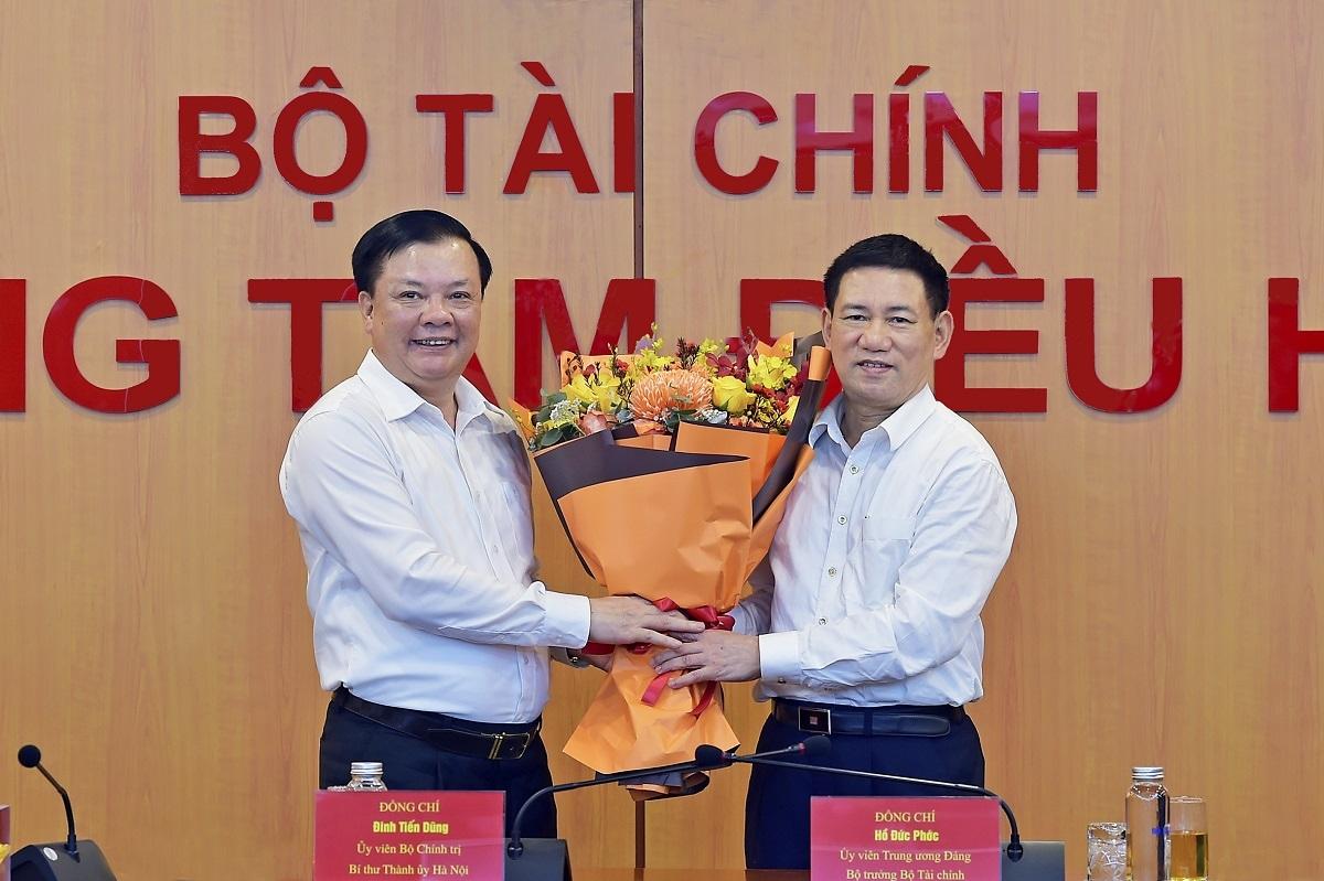 Bộ trưởng Bộ Tài chính Hồ Đức Phớc tặng hoa Bí thư Thành ủy Hà Nội Đinh Tiến Dũng.