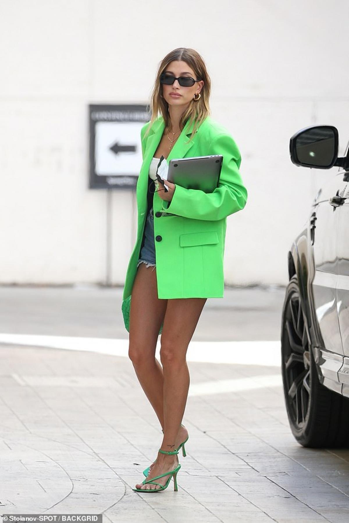 Bà xã Justin Bieber diện áo blazer màu xanh neon nổi bật phối cùng quần shorts jeans, khoe khéo đôi chân thon dài gợi cảm.