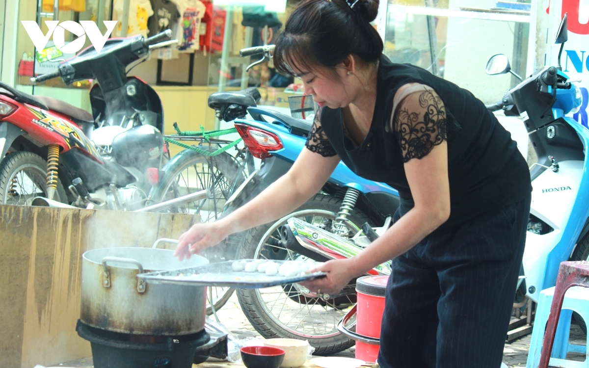 """A trader cooks """"banh troi"""" and """"banh chay"""" on the pavement."""
