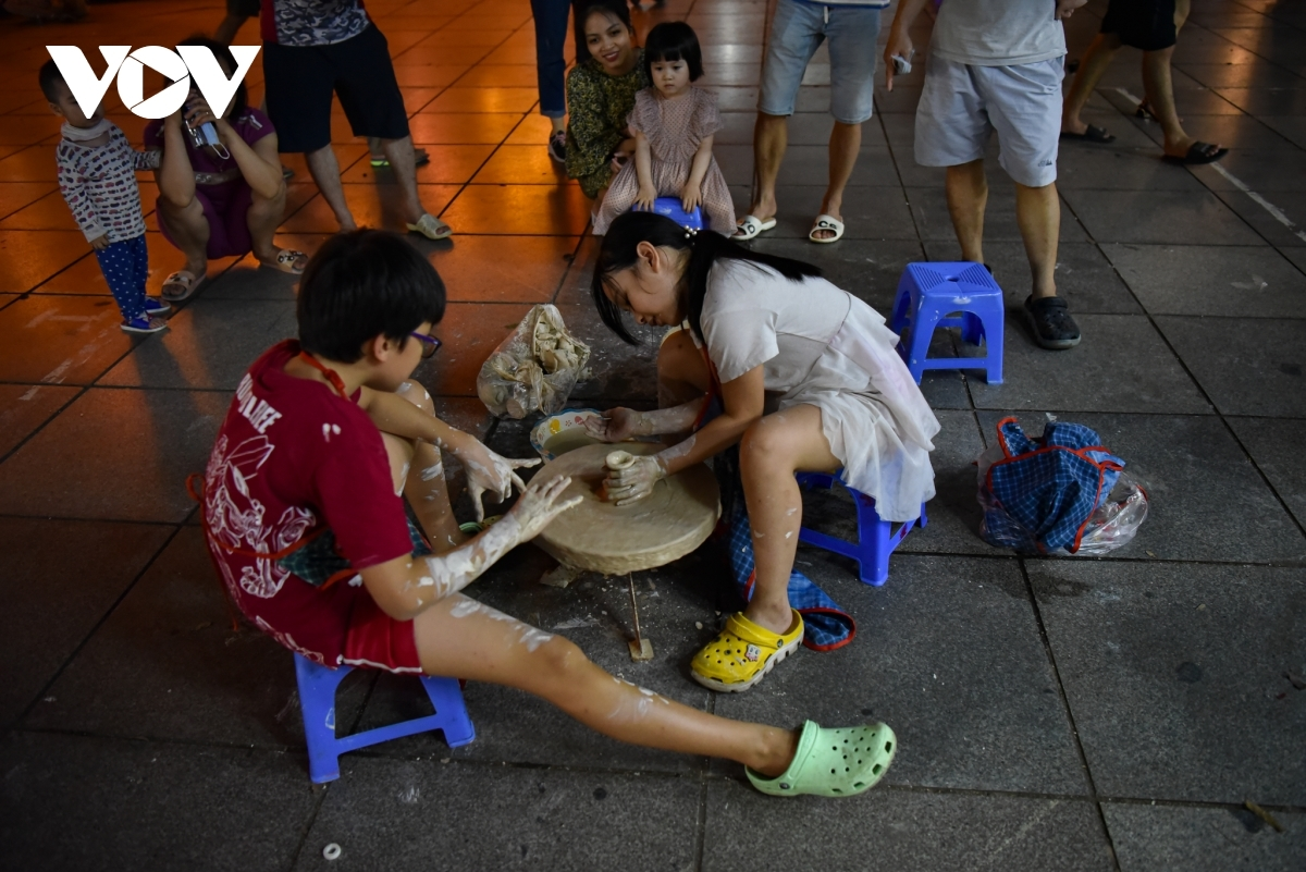 Children are given the chance to produce ceramic items at a booth situated in the Bat Trang ceramic village pavilion.