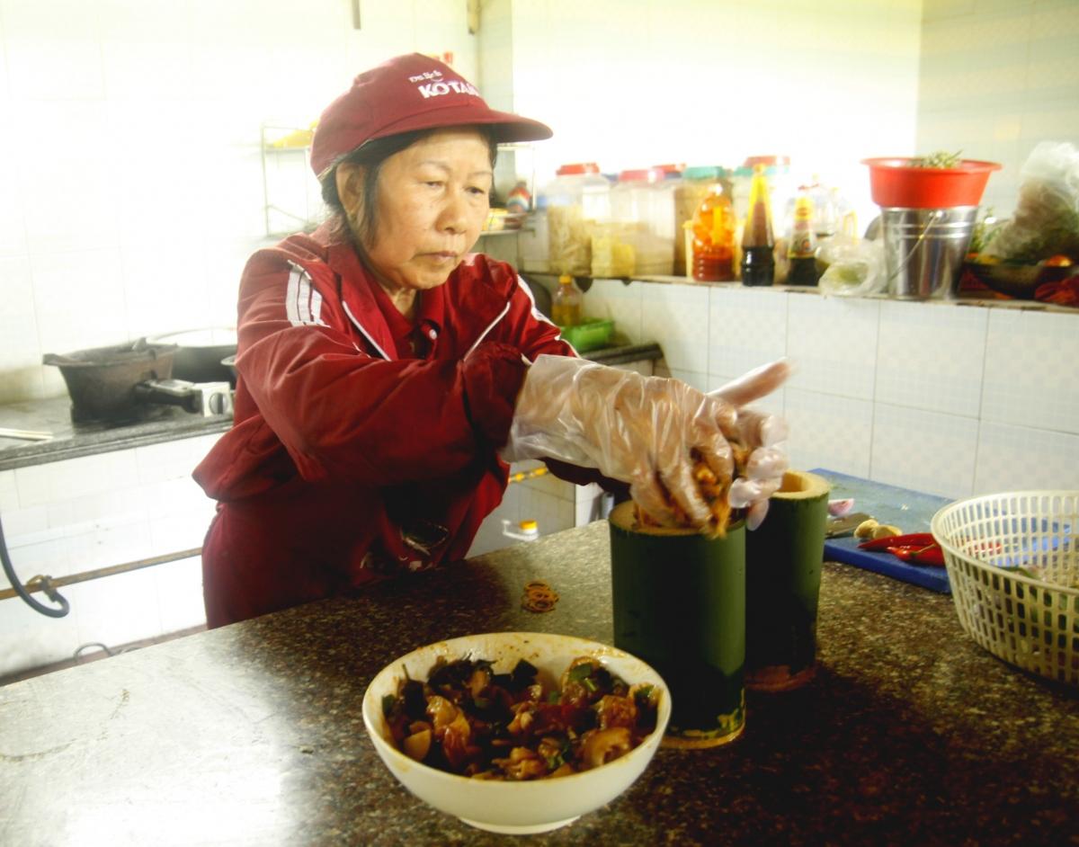 Sau khi tẩm ướp gia vị, thịt heo được bỏ vào ống tre tươi.