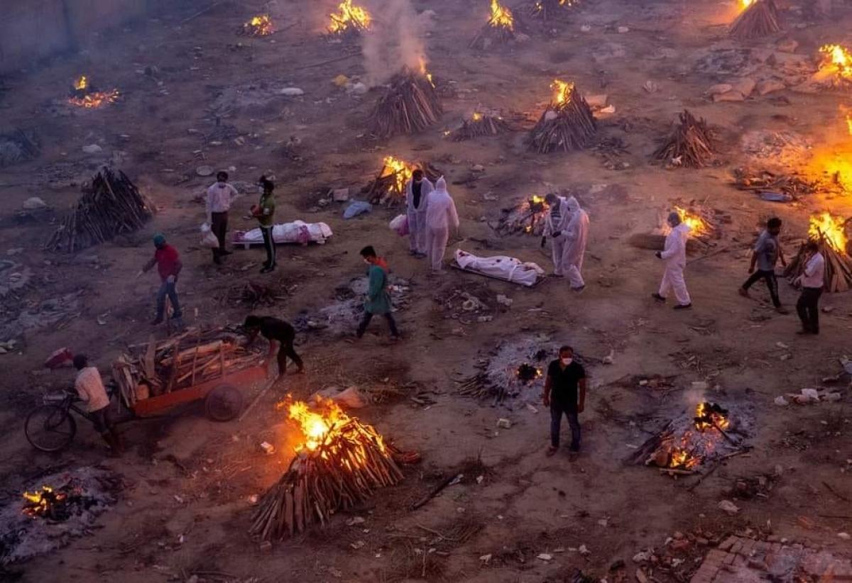 Cảnh tượng thương tâm tại một bãi hỏa táng ở Ấn Độ: Xe chở củi đến. Các thi thể nằm trên mặt đất chờ thiêu. Các giàn thiêu khác đang bốc cháy ngùn ngut. Ảnh: Reuters.