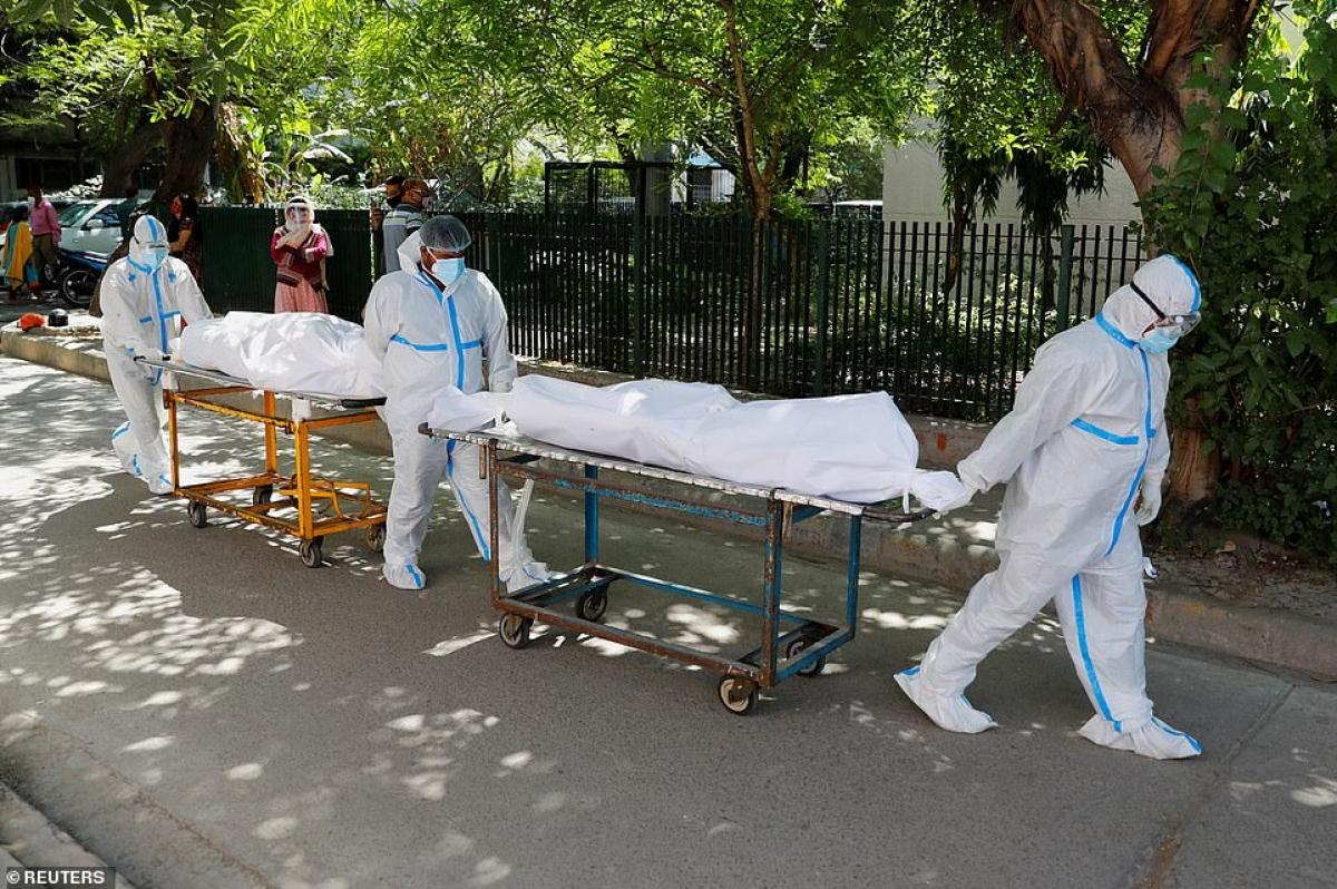 Vận chuyển thi thể nạn nhận Covid-19 bằng cáng có bánh xe bên ngoài một bệnh viện ở thủ đô New Delhi, Ấn Độ.