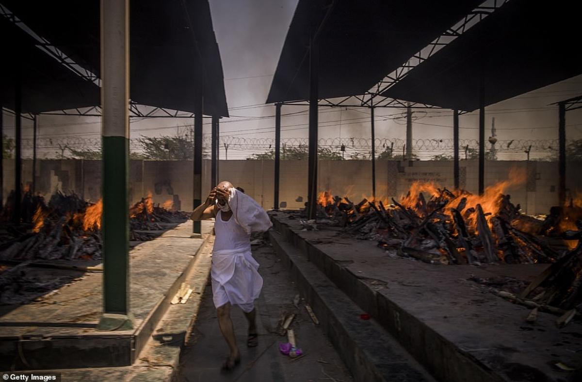 Thầy tu lấy tay che mặt chạy đi trong lúc nhiều giàn hỏa thiêu đang bốc cháy.