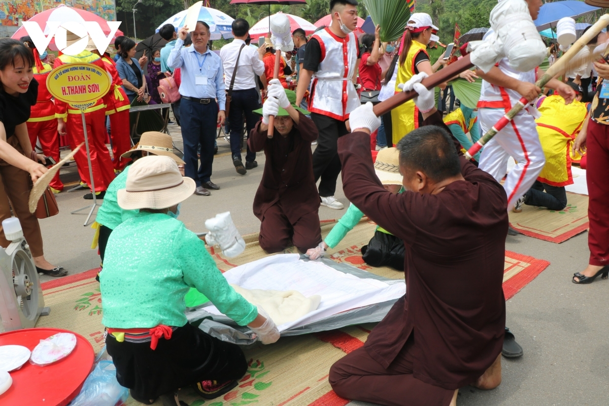 The contestants pound the sticky rice in order to make Banh Giay.