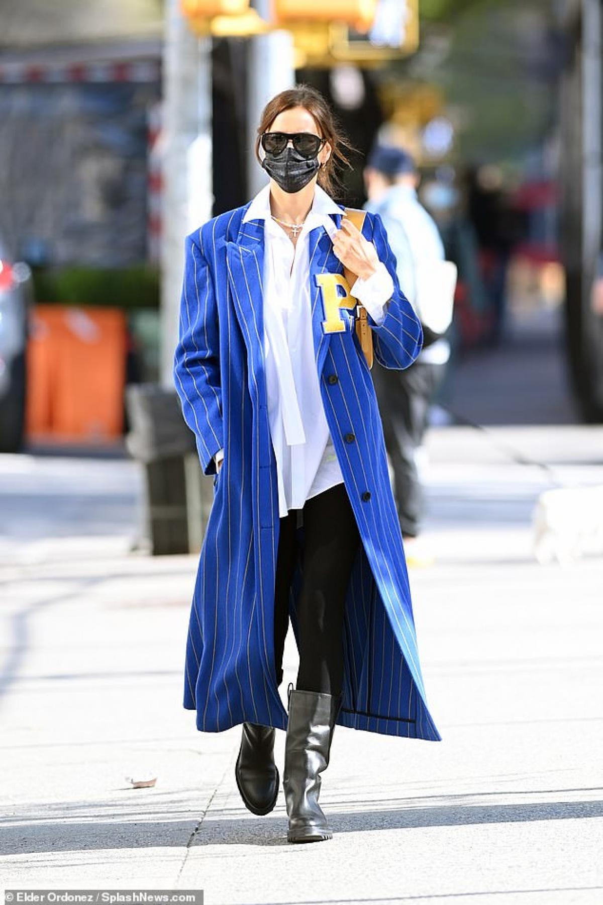 Siêu mẫu Nga diện áo khoác dáng dài kẻ sọc màu xanh nổi bật, phối cùng bốt hàng hiệu sang chảnh.