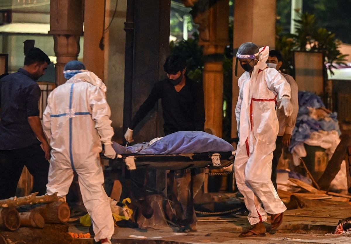 Người thân mang xác nạn nhân tử vong do Covid-19 đi hỏa táng tại Nigambodh Ghat, bên bờ sông Yamuna, New Delhi vào rạng sáng ngày 22/4/2021. Ảnh: AFP