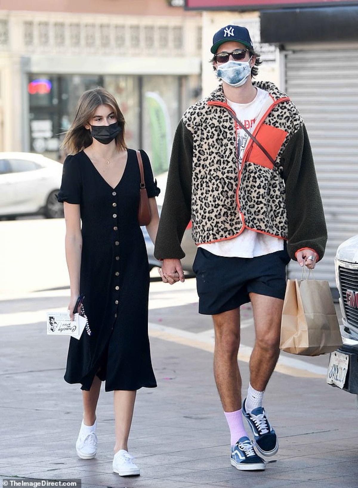Cặp đôi tay trong tay sánh bước trên phố.