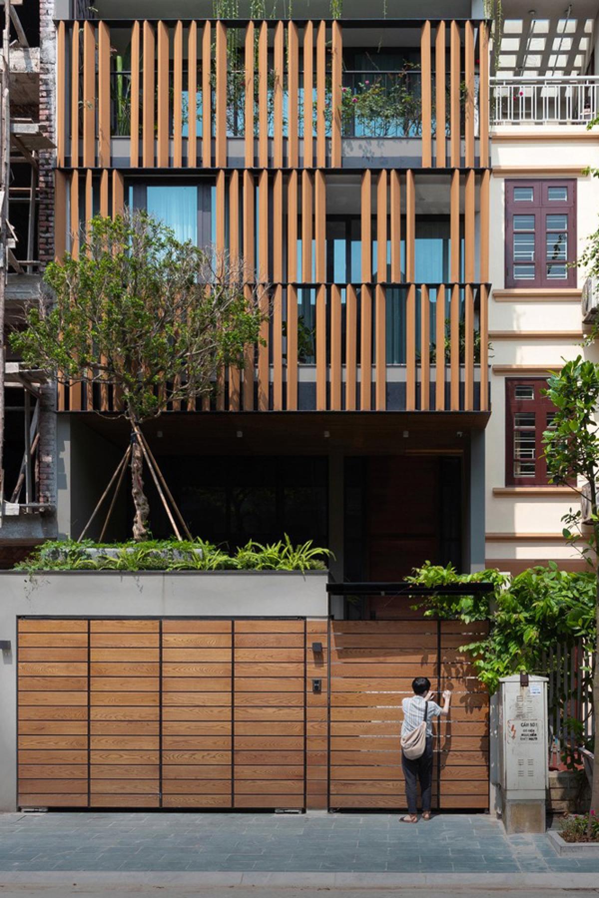 Công trình nằm ở quận Long Biên, Hà Nội, có cấu trúc của một ngôi nhà phố với hai mặt thoáng trước và sau. Các kiến trúc sư thiết kế đưa ra một hình ảnh ngôi nhà hiện đại mà vẫn gần gũi nhờ chất liệu gỗ ở hệ cổng và lam mặt tiền.