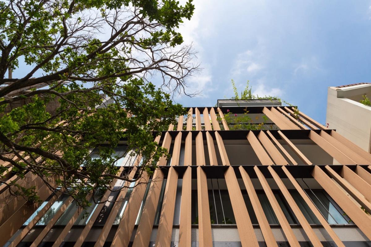Do ngôi nhà quay hướng tây nên hệ lam gỗ được bố trí vừa góp phần ngăn bức xạ nhiệt, vừa có vai trò định hình công trình. Tận dụng một phần tầng trệt để xe, mảnh vườn trên mái của khối kiến trúc này tạo nên một không gian xanh thoáng đãng với cây vươn cao trước nhà.