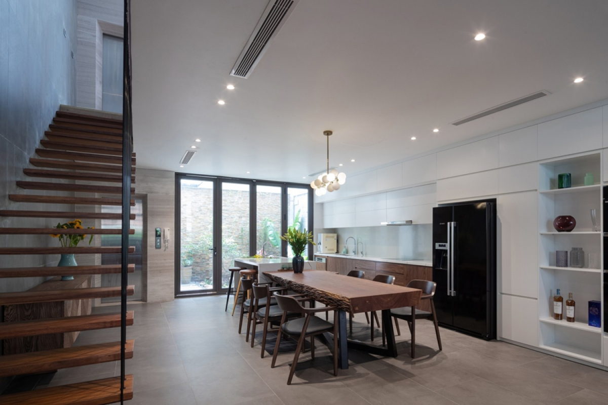 Bếp và phòng ăn nằm ở phía sau kết nối với một sân vườn nhỏ sau nhà. Hệ tủ bếp hiện đại phối màu trắng – nâu tạo nên sự hài hòa. Ngôi nhà còn được trang bị thang máy ở phía góc nhà để tăng sự tiện lợi trong sử dụng, sinh hoạt.