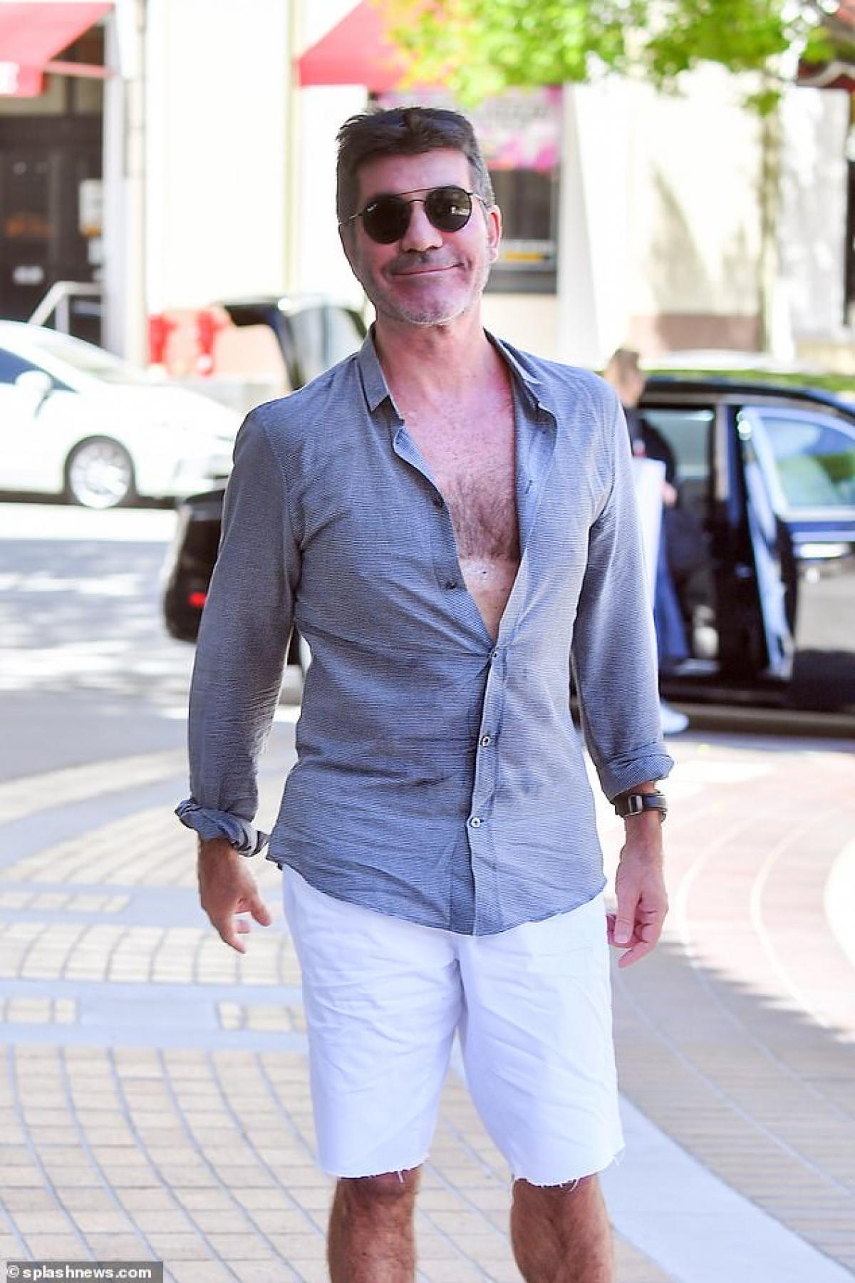 Simon Cowell tươi cười khi bắt gặp ống kính máy ảnh của cánh paparazzi hướng về phía mình.