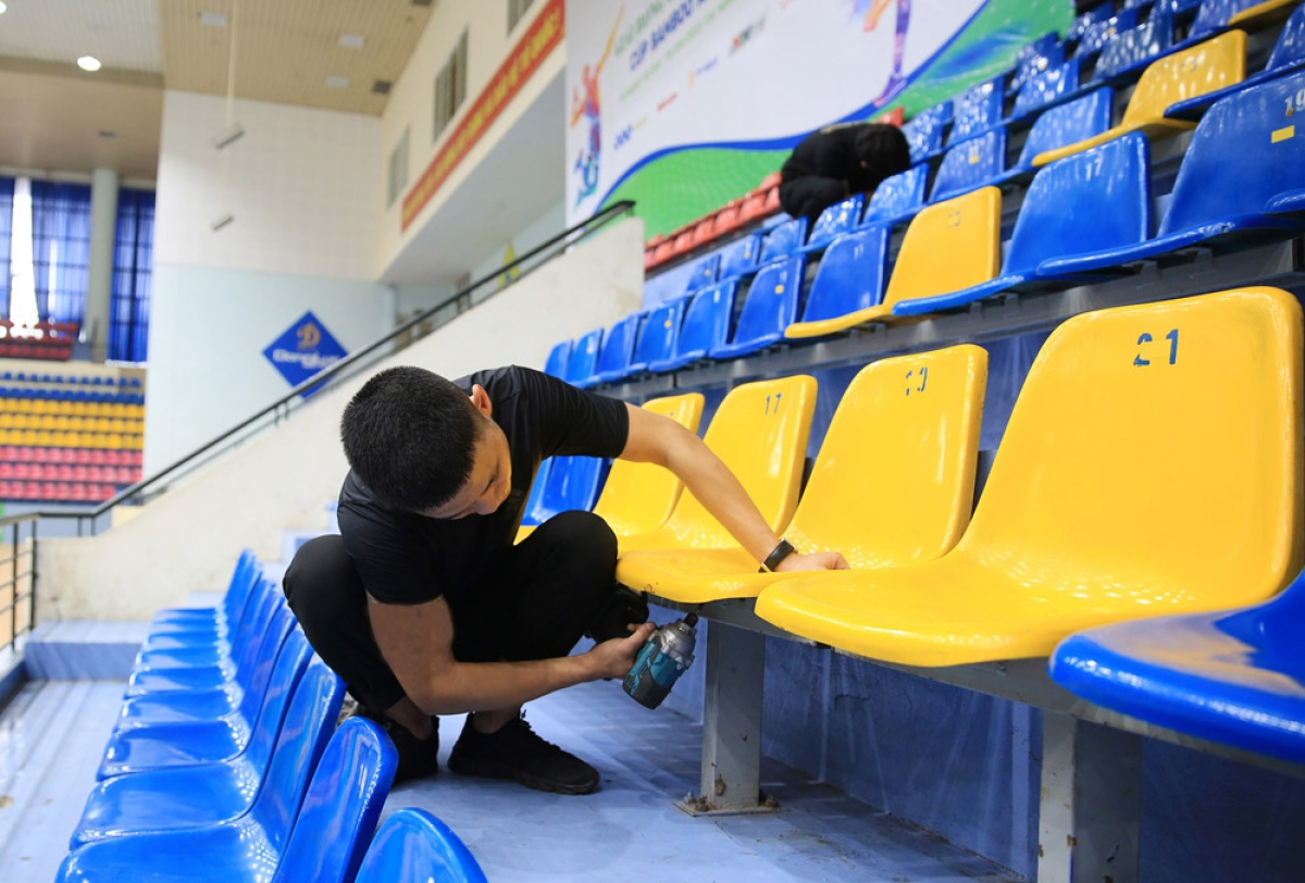 A worker is finalizing seat repair at the Gia Lam competition hall, the venue of the wrestling event.