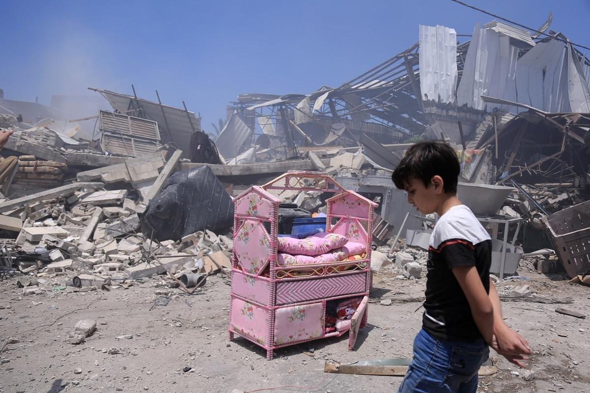 Một cậu bé Palestine đứng trước căn nhà đổ nát của mình tại Dải Gaza vào ngày 14/5 sau trận không kích của Israel. Ảnh:The New York Times