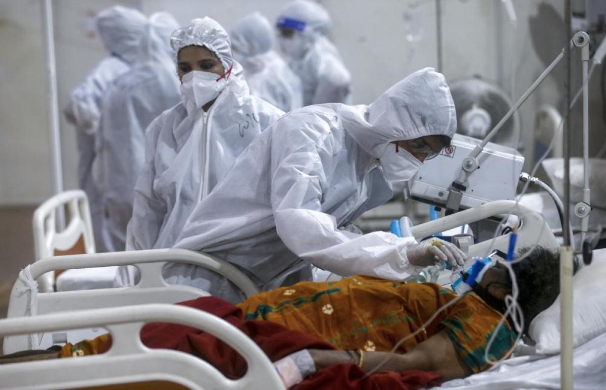 Bên trong bệnh viện dã chiến BKC ở Mumbai, một nhân viên y tế điều chỉnh mặt nạ dưỡng khí cho một bệnh nhân Covid-19. Các bác sĩ, y tá và chuyên gia tại bệnh viện theo dõi sát sao và điều trị cho hàng trăm bệnh nhân.