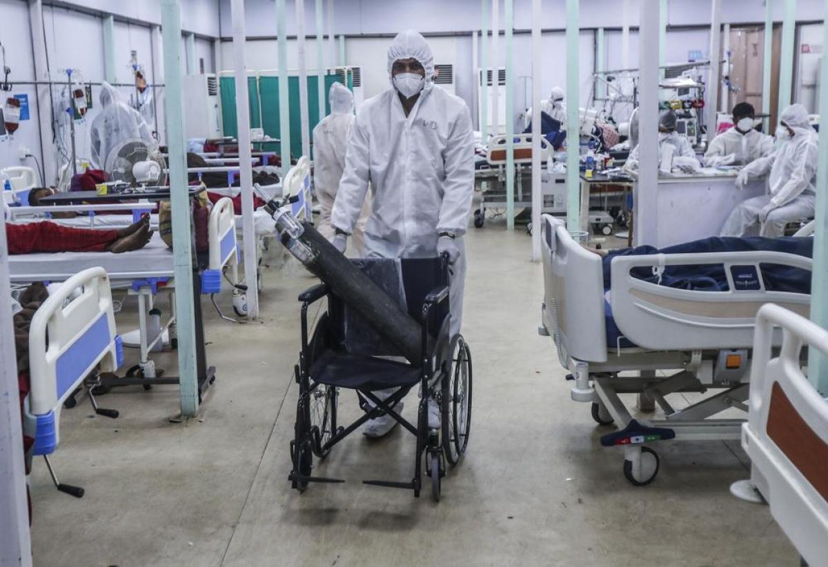 Một nhân viên y tế di chuyển bình oxy bằng xe lăn.