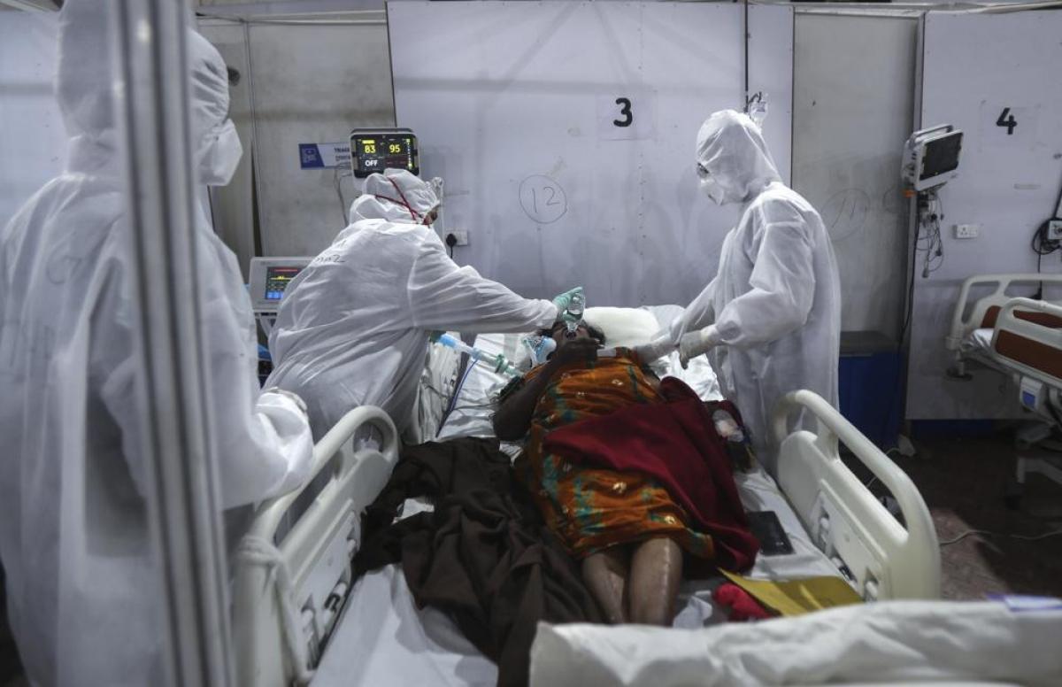 Nhân viên y tế cho một bệnh nhân uống nước.