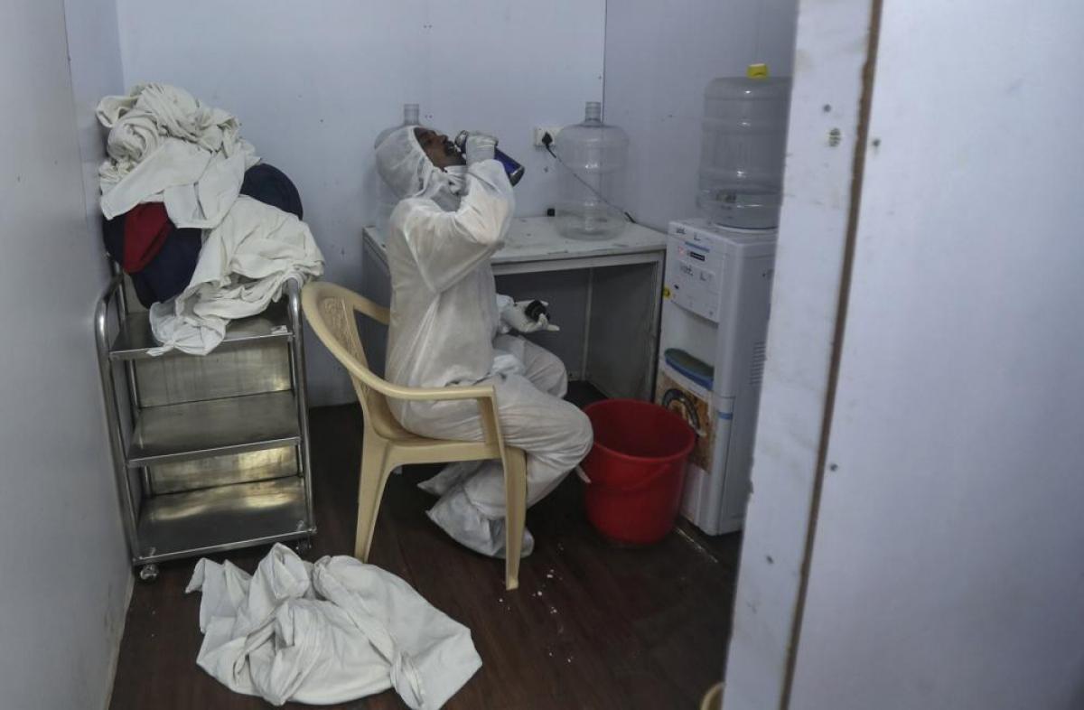 Một nhân viên y tế nghỉ ngơi sau giờ làm việc tại bệnh viện dã chiến BKC./.