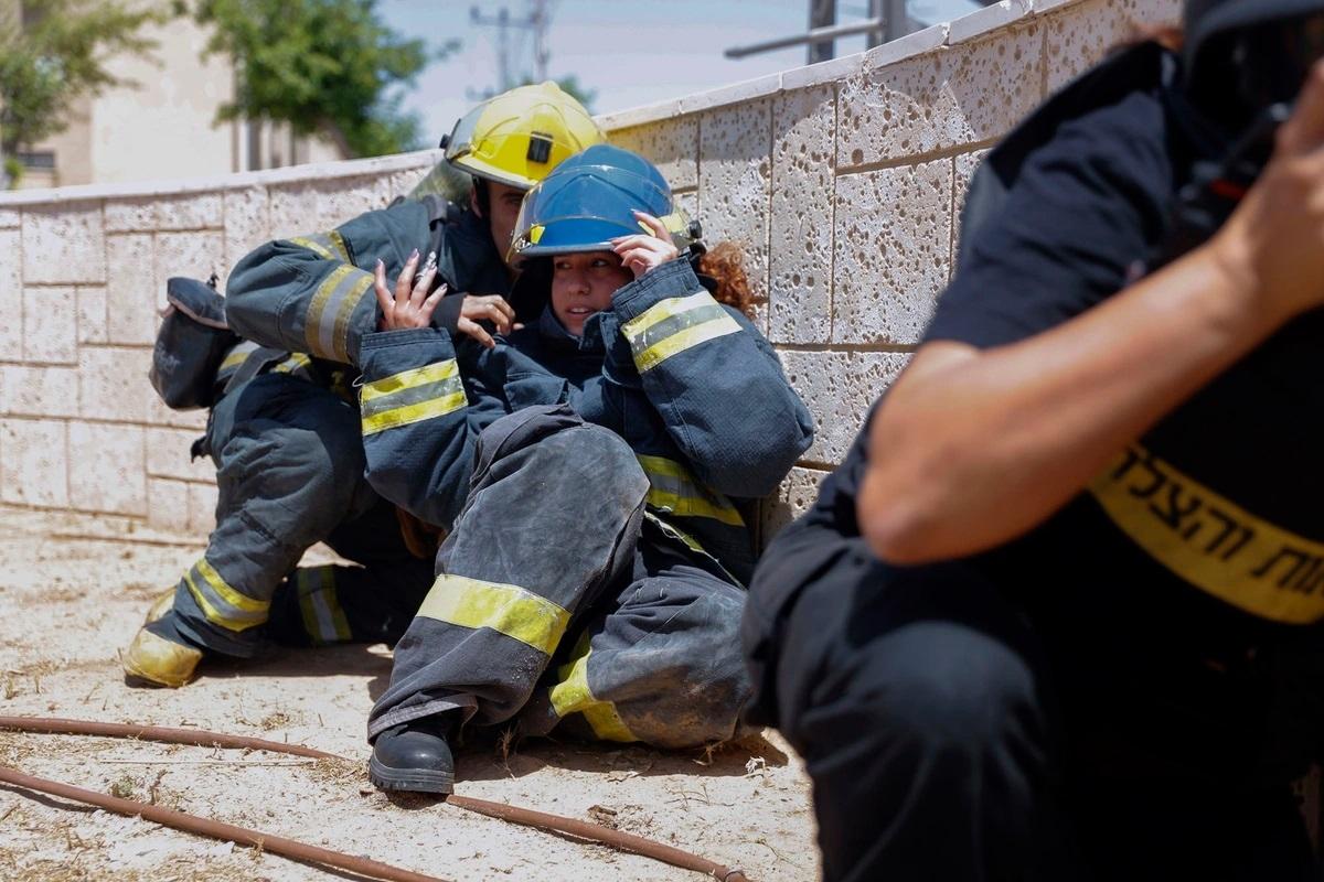 Nhân viên cứu hỏa Israel vội ngồi sụp xuống khi có rocket Palestine phóng tới. Ảnh: AP.
