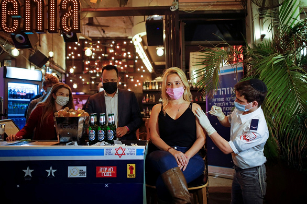 Một nhân viên y tế ở Tel Aviv, Israel tiêm vaccine ngừa Covid-19 cho người dân ngày 18/2. Tất cả người đến tiêm chủng được quán bar địa phương mời nước uống miễn phí. Ảnh: Reuters