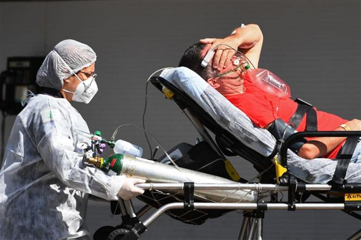 Nhân viên y tế chuyển bệnh nhân COVID-19 tới bệnh viện điều trị ở Brasilia, Brazil, ngày 15/3/2021. Ảnh: AFP/TTXVN
