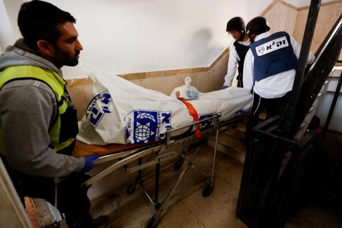 Nhân viên y tế di chuyển thi thể một nam giới tử vong do rocket của Hamas. Địa điểm này là thành phố Ashkelon (miền nam Israel). Ảnh: Reuters.