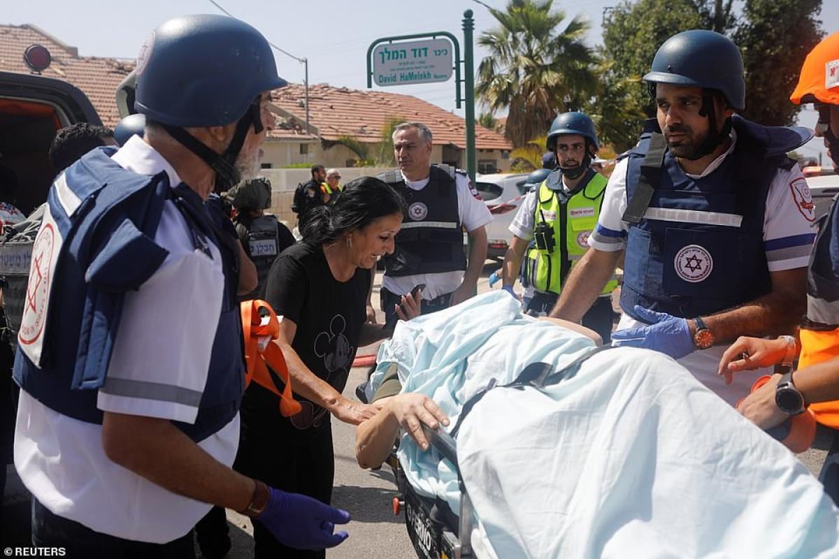 Nhân viên y tế Israel sơ tán một người bị thương do rocket phóng từ Gaza sang. Ảnh: Reuters.