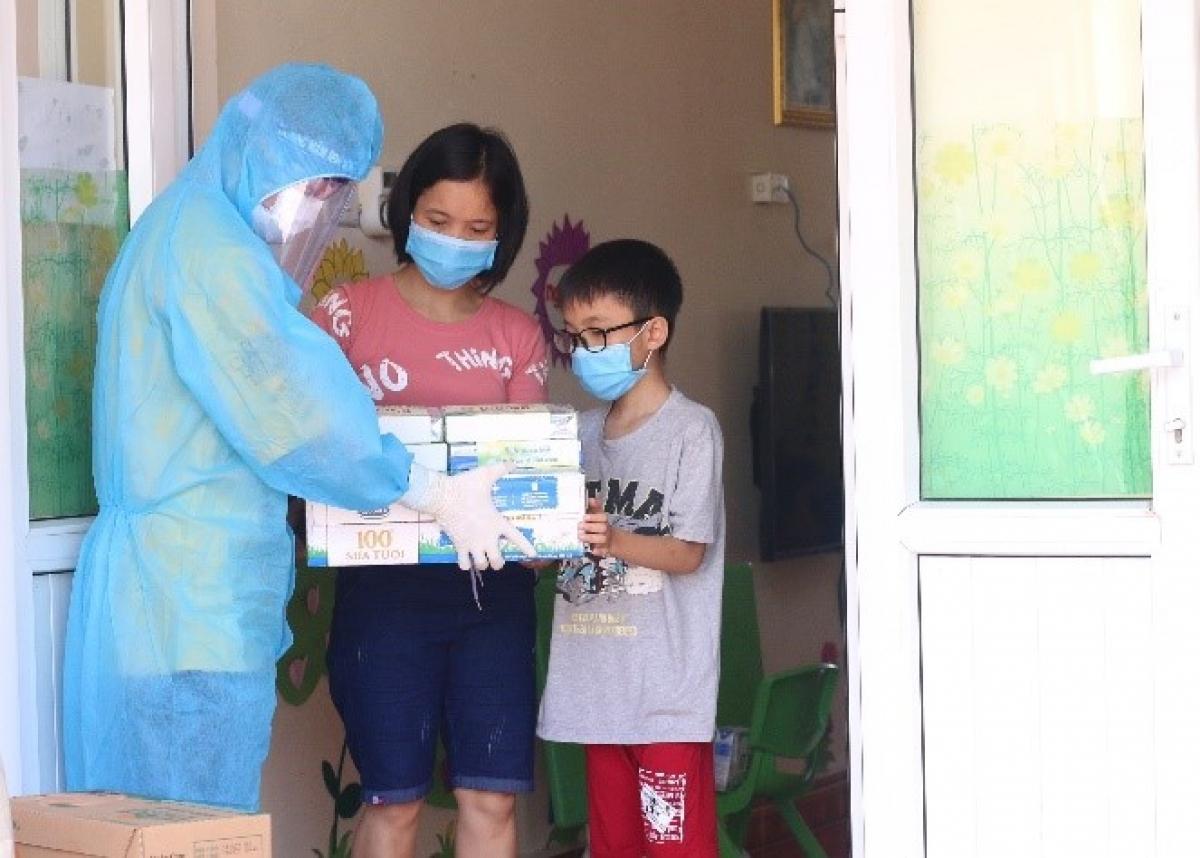 Người dân, trẻ em trong nơi cách ly tập trung tại huyện Thuận Thành, một trong những điểm nóng về dịch ở Bắc Ninh, đón nhận món quà từ Vinamilk.