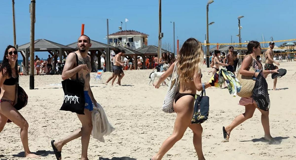 Khi còi báo động về rocket Hamas phóng tới, người dân Israel đang thư giãn trên bờ biển thành phố Tel Aviv cũng phải tất tả chạy đi sơ tán như thế này. Ảnh: AFP.