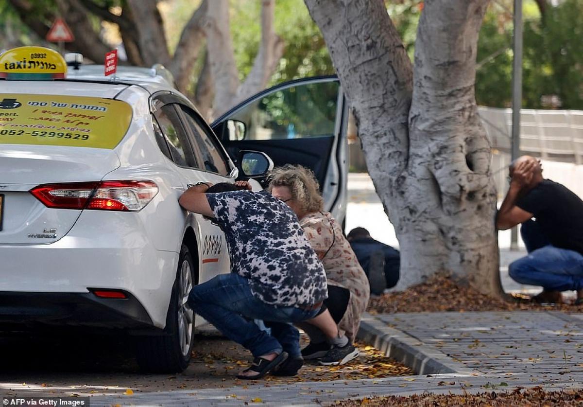 Vội trú tránh sau ô tô con và gốc cây khi đang ở ngoài đường và chưa tìm được hầm trú ẩn mà rocket đang bay đầy bầu trời. Ảnh: AFP.