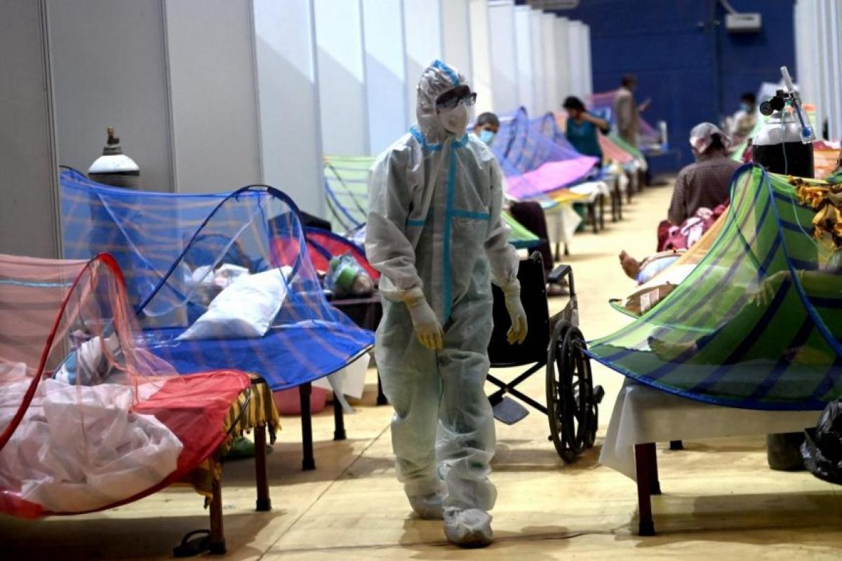 Một nhân viên y tế đi qua các giường bệnh tại sân vận động Common Wealth Games được chuyển đổi thành trung tâm điều trị Covid-19 tại New Delhi ngày 5/5/2021. Ảnh: AFP