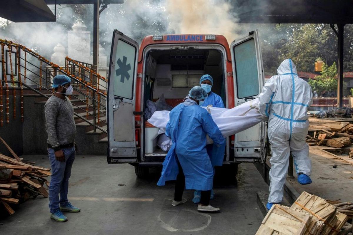 Các nhân viên y tế chuyển thi thể một bệnh nhân Covid-19 lên xe cứu thương để đưa tới địa điểm hỏa táng ở New Delhi, Ấn Độ. Ảnh: Reuters
