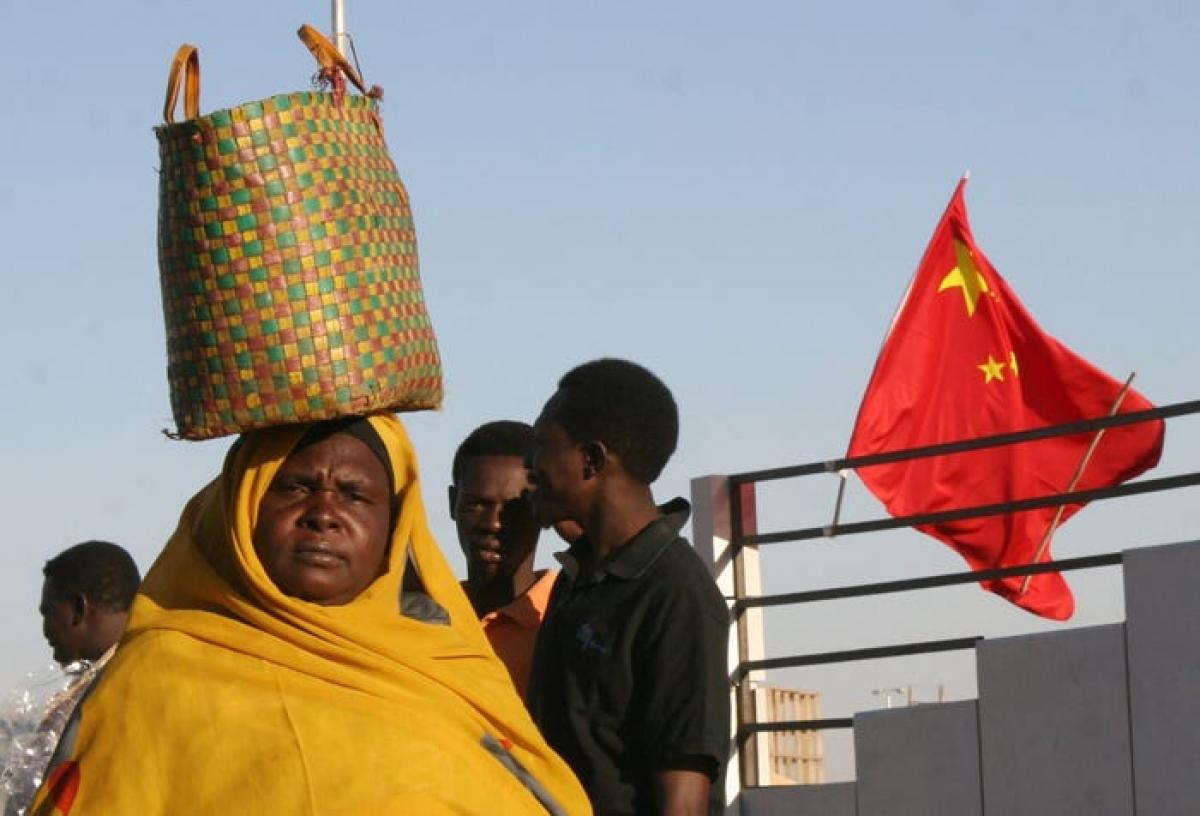 Một người phụ nữ Sudan đi qua một lá cờ Trung Quốc treo trên đường phố ở Khartoum ngày 1/2/2007. Ảnh: AP