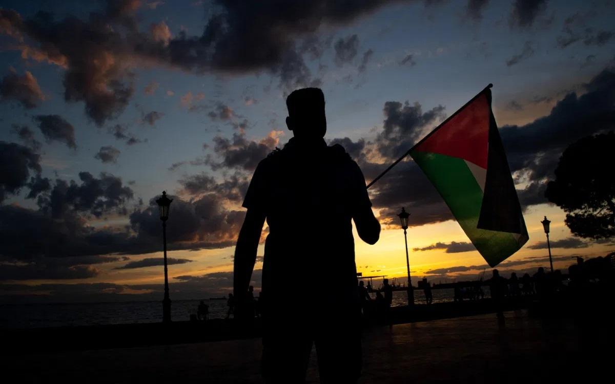 Một nam giới cầm cờ Palestine trong một cuộc biểu tình thân Palestine. Ảnh: NurPhoto.