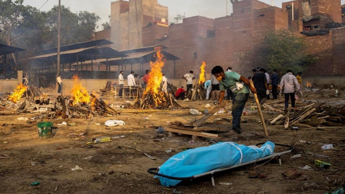 Một người đàn ông đang chuẩn bị giàn lửa hỏa thiêu thi thể 1 nạn nhân Covid-19 ngay bên cạnh. Ảnh: Reuters