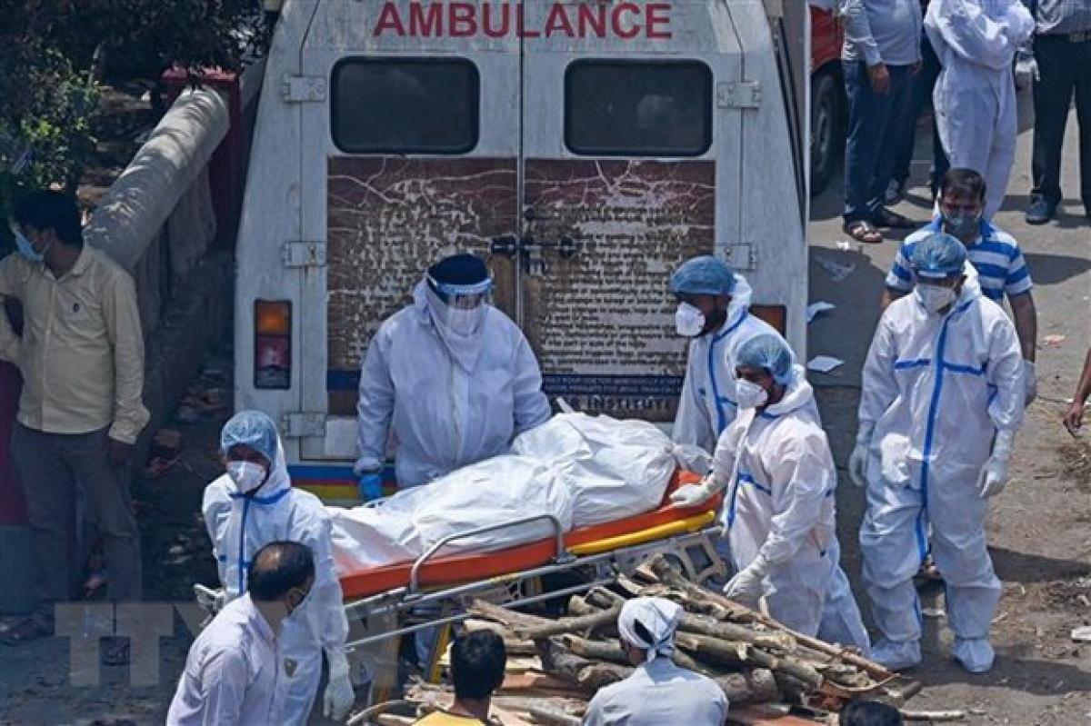 Nhân viên y tế chuyển thi thể bệnh nhân COVID-19 tới khu hỏa táng ở New Delhi, Ấn Độ. (Ảnh: AFP/TTXVN).