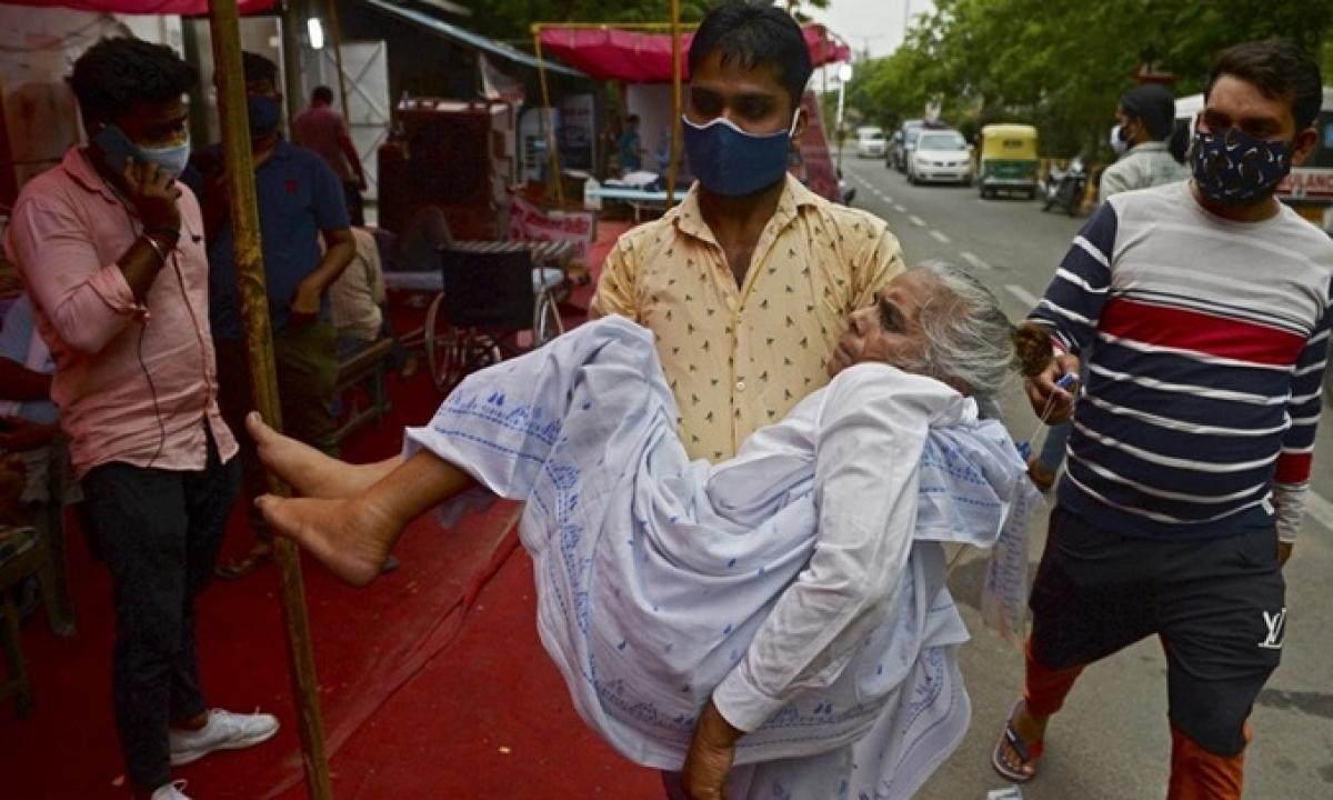 Người thân đưa bệnh nhân Covid-19 bị khó thở đến trung tâm hỗ trợ oxy miễn phí ở ngoại ô New Delhi, Ấn Độ hôm 10/5. Ảnh:AFP.