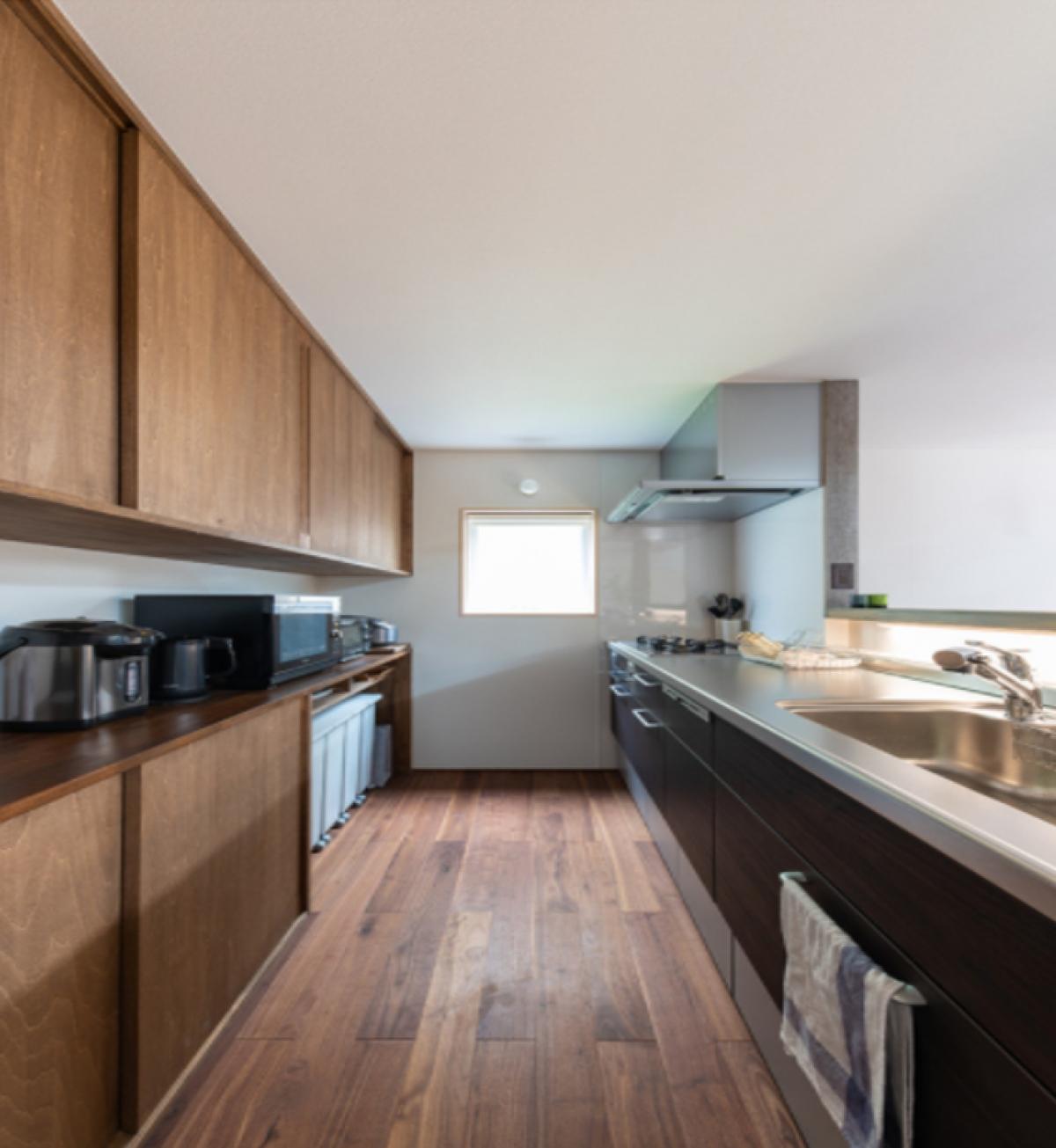 Căn bếp sử dụng nhiều chất liệu gỗ óc chó tự nhiên theo yêu cầu của gia chủ để phù hợp với nội thất căn nhà. Khu bếp cũng có nhiều không gian chứa đồ và được thiết kế chỗ để sọt rác kín. Thiết kế rất phù hợp và tiện dụng với gia chủ - một người yêu nấu ăn và dành nhiều thời gian cho công việc bếp núc.(Địa điểm nhà: Niigata, Nhật Bản)