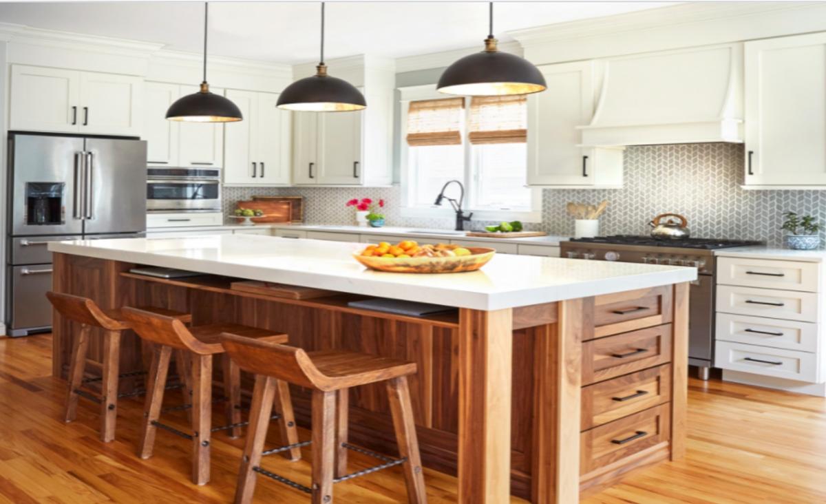 Căn phòng bếp tại bang Maryland, Mỹ, này có nhiều chi tiết thiết kế hấp dẫn. Những tủ và quầy bếp dài màu trắng tạo cảm giác nhẹ nhàng và thoáng đãng trong khi tấm ốp gốm màu xám tạo thêm sự chuyển động và hoa văn. Quầy bếp làm bằng gỗ óc chó được thiết kế tỉ mỉ, tinh tế là trung tâm của căn bếp. Một kệ mỏng bên dưới mặt bàn bằng thạch anh tạo không gian để laptop và các công cụ khác để làm việc tại nhà. Ổ cắm điện được bố trí phía sau kệ cho phép gia chủ sạc các thiết bị, trong khi ngăn kéo để giấy và các vật dụng khác.
