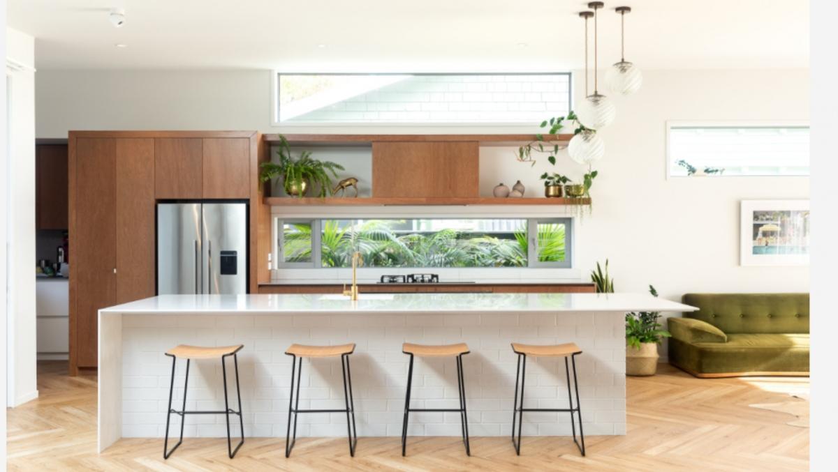 Căn bếp sử dụng một màu trắng kết hợp với màu gỗ đơn giản, bố trí các cửa sổ hẹp (hài hòa với các hình dáng của tủ và quầy, bàn bếp) lấy ánh sáng. Khu vực nấu ăn được bố trí tầm nhìn hướng ra vườn, mang lại sự kết nối hài hòa với thiên nhiên. Chúng ta có thể thấy tại sao căn bếp thân thiện, tươi mới, nhẹ nhàng này lại hấp dẫn độc giả Houzz đến vậy.