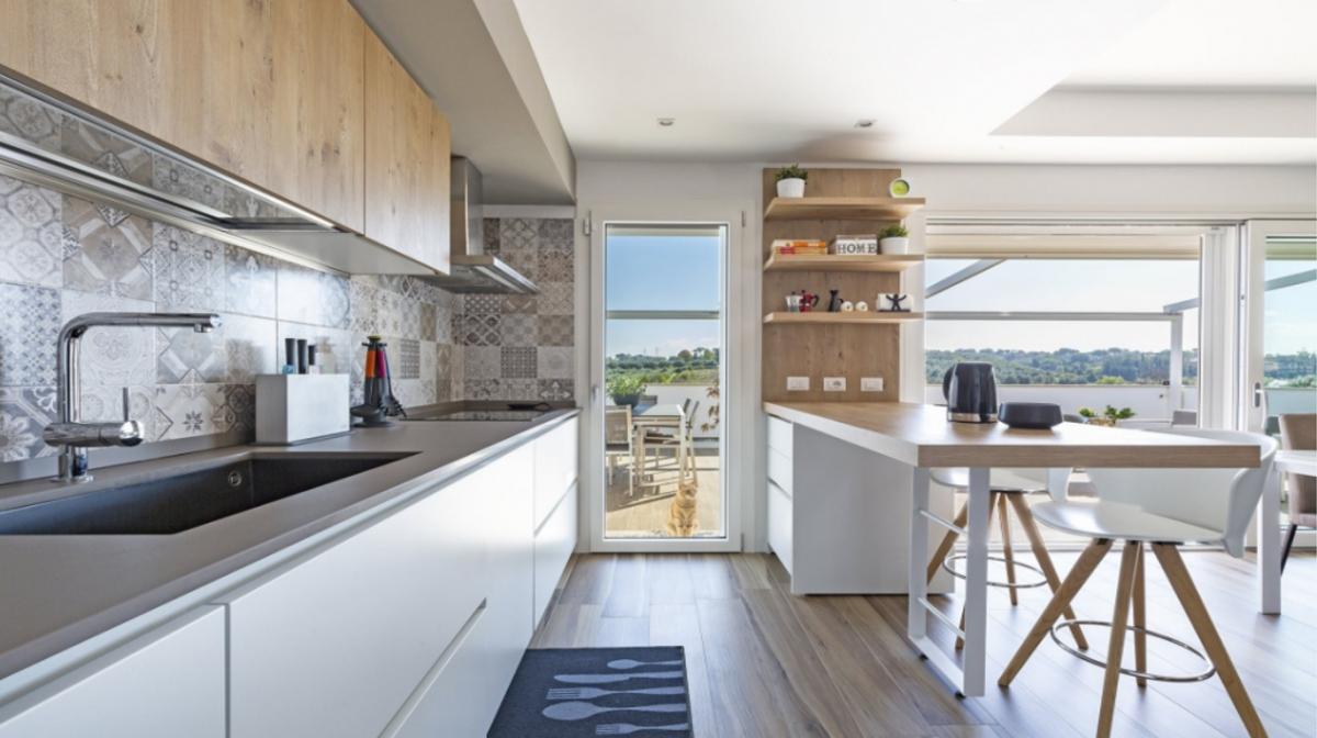 """Căn bếp mang phong cách Ý đậm nét và thể hiện xu thế thịnh hành ở Italia hiện nay: sự kết hợp của màu nền trắng với màu gỗ tự nhiên, của không gian sáng màu với các gạch lát có họa tiết được lựa chọn kỹ càng. Căn bếp không chỉ có tầm nhìn đẹp mà còn có một lối đi ra ban công. Nếu là chủ nhân của căn bếp này, bạn chắc hẳn không ngạc nhiên khi biết rằng """"bếp có tầm nhìn đẹp"""" là một trong những cụm từ được tìm kiếm nhiều nhất tại Italia hiện nay."""
