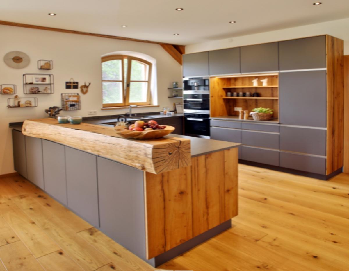 Gam màu ghi xám ở các bề mặt phía trước đang là màu sắc thịnh hành tại nước Đức nhưng sử dụng chất liệu gỗ tự nhiên lại là phong cách cổ điển đậm nét. Đây là cách mà các kiến trúc sư đáp ứng mong muốn của khách hàng về việc kết hợp giữa thiết kế hiện đại, chức năng làm bếp, không gian cất trữ đồ đạc và nét quyến rũ của một tòa nhà cổ. Thanh gỗ ngang trên mặt bàn bếp cũng mang một nét tinh tế riêng: Nó được chế tác từ thân một cây sồi già, mọc ngay trong khuôn viên nhà của gia chủ.(Địa điểm nhà: Munich, Đức)